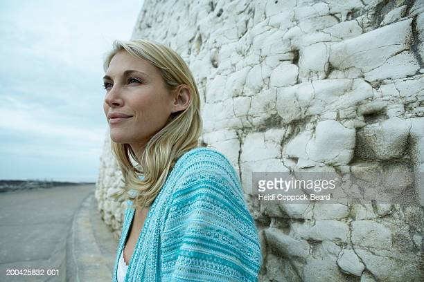 woman by rock wall, sea in background - heidi coppock beard stock-fotos und bilder