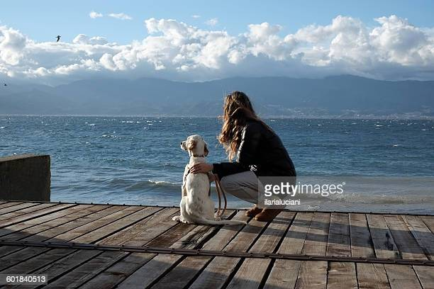 Woman by sea crouching next to her dog, Reggio di Calabria, Italy