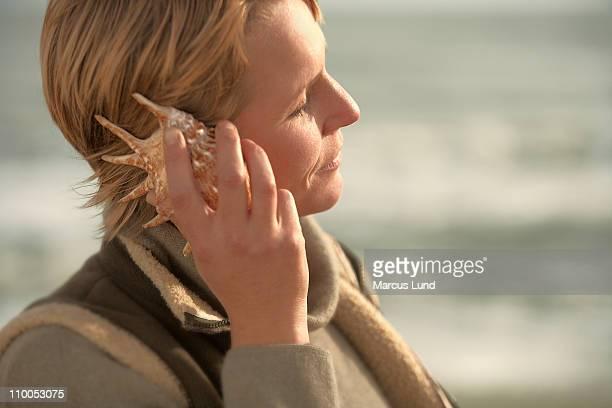 woman by sea, listening in seashell - alleen één mid volwassen vrouw stockfoto's en -beelden