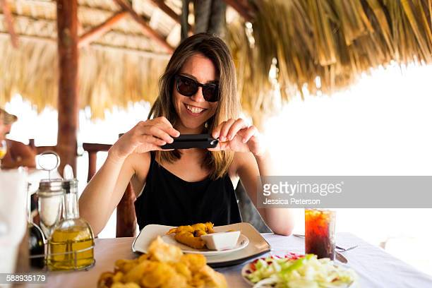 Woman by table, using phone