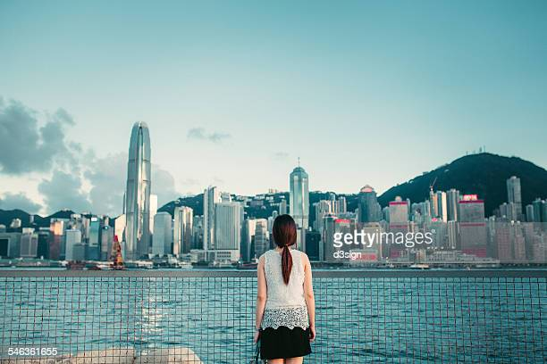 Woman by the harbour looking away to urban skyline