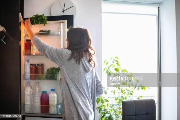 woman by the open fridge taking a bunch of parsley - refrigerator stock pictures, royalty-free photos & images