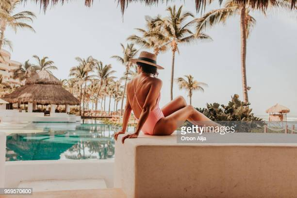 woman by the pool - women sunbathing stock photos and pictures