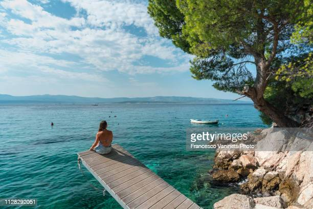 woman by the sea, brac island, croatia. - tranquil scene stock pictures, royalty-free photos & images