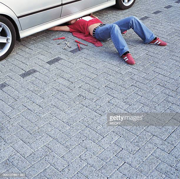 woman by tools, partially lying under car, arms outstretched - unterhalb stock-fotos und bilder