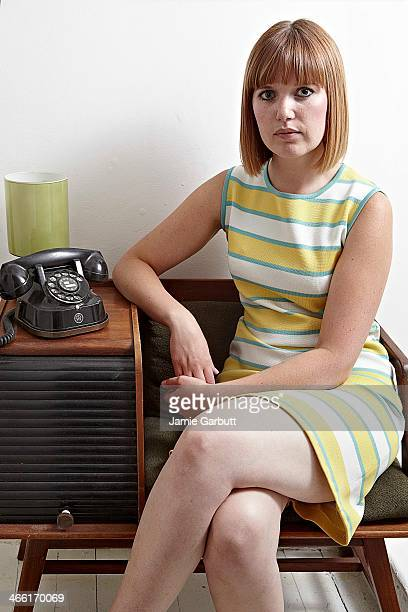 Woman by vintage telephone looking to camera.