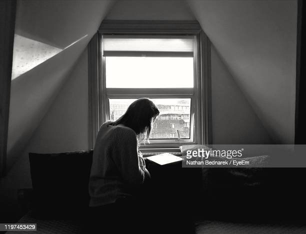 woman by window at home - black and white stock pictures, royalty-free photos & images