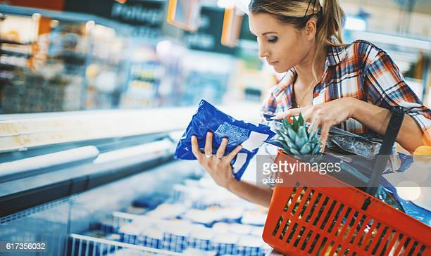 woman bying some frozen food at a supermarket. - convenience stock photos and pictures