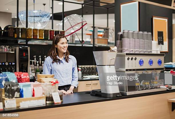 Woman cafe clerk standing at the counter