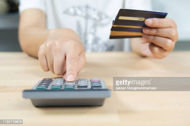 woman calculate how much cost or spending have with credit cards - fee stock pictures, royalty-free photos & images