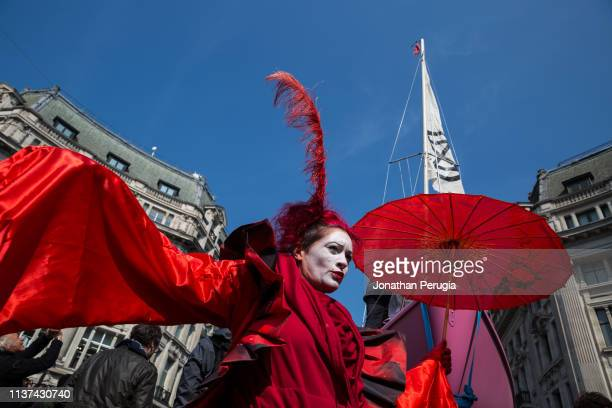 A woman called 'Red Sarah' dances in front of a pink yacht parked in the middle of Oxford Circus during a protest against climate change on 15th...