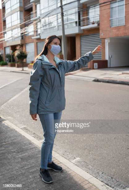 woman calling a taxi on the street wearing a facemask - request stock pictures, royalty-free photos & images