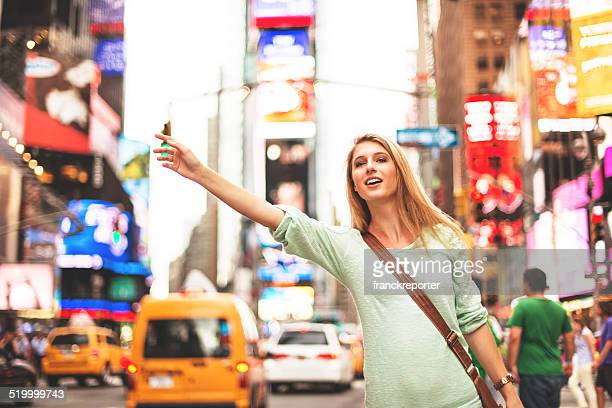 woman calling a taxi on times square - NYC