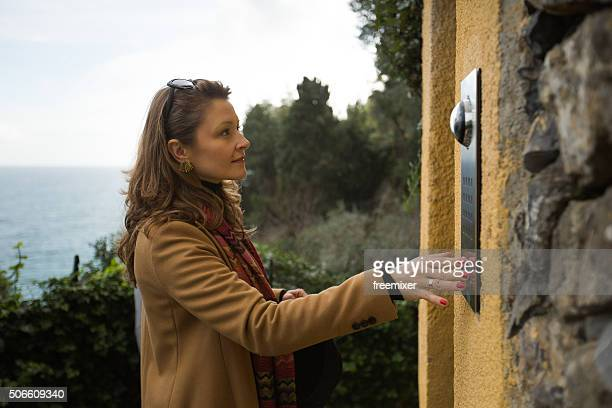 woman calling by the intercom on a house - intercom stock photos and pictures