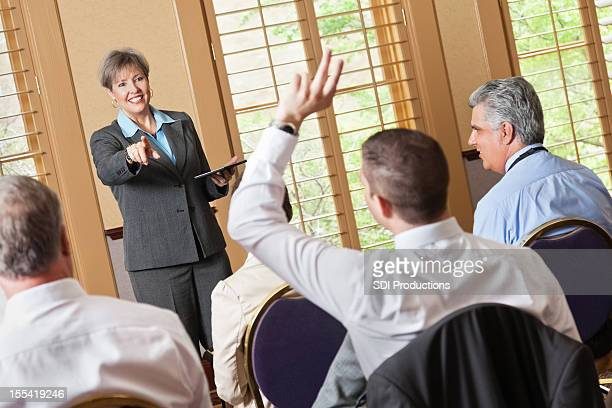Woman calling on question during business presentation or conference