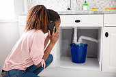 Woman Calling Plumber In Front Of Leaking Sink Pipe