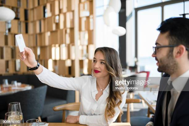 Woman calling waiter to pay for lunch