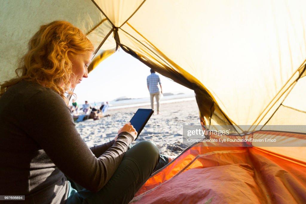 Woman camping using smart phone on beach at sunset : Stock Photo