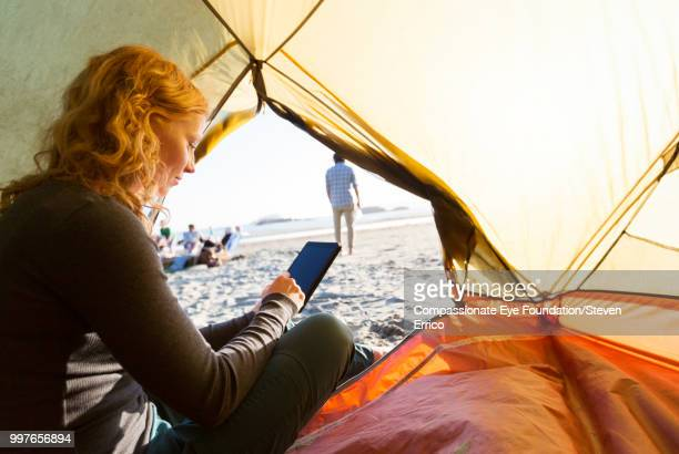 Woman camping using smart phone on beach at sunset