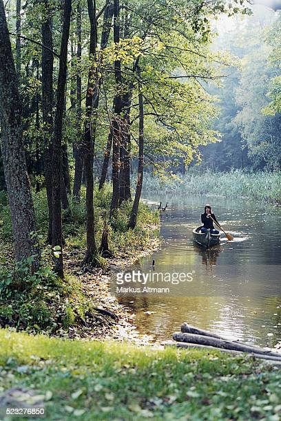 Woman canoeing down a river