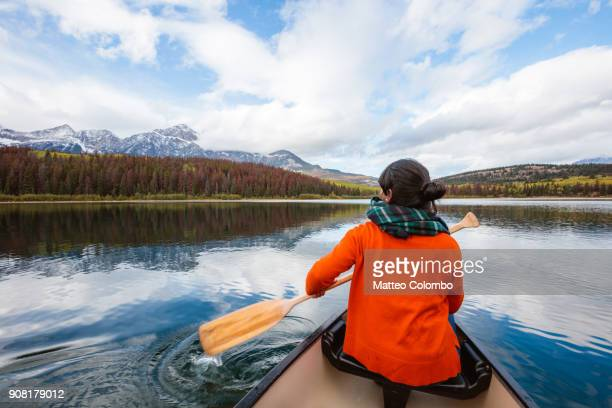 woman canoeing on lake, jasper national park, canada - canadian rockies stockfoto's en -beelden