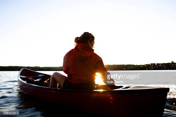 A woman canoes on Cobbosseecontee Lake, in southern Maine.