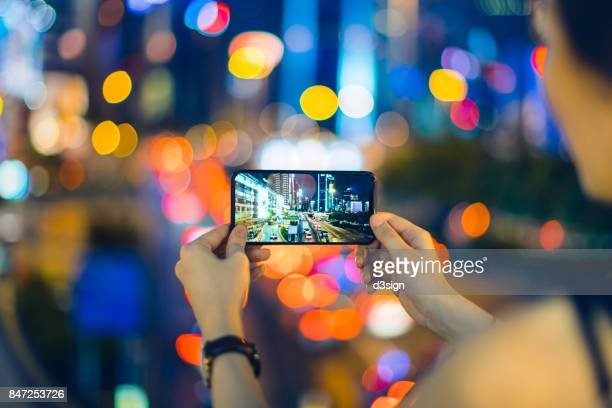 Woman capturing city night scene with smartphone against illuminated street lights