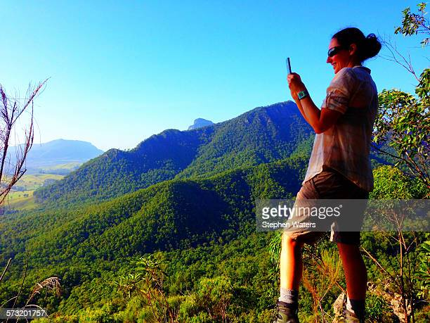 Woman capturing image with smart phone Mt Barney Queensland Australia