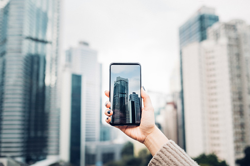 Woman capturing modern city view with smartphone against cityscape - gettyimageskorea