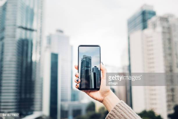 Woman capturing modern city view with smartphone against cityscape