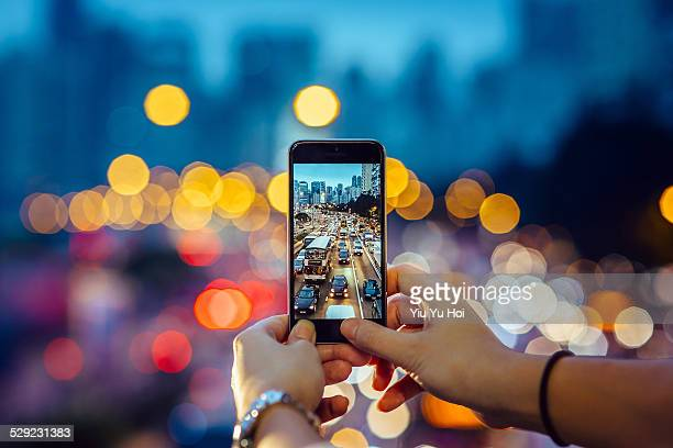 woman capturing the busy traffic with smartphone - photography themes stock pictures, royalty-free photos & images