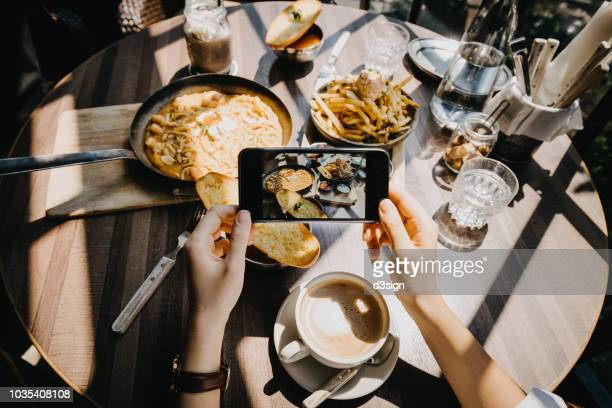 Woman capturing the snapshots of an enjoyable meal with friends by smartphone in restaurant