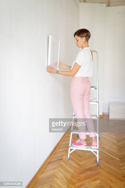 Woman carefully adjusting painingt