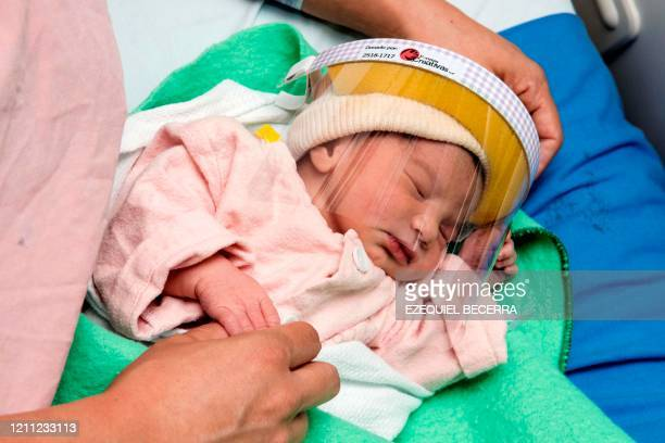 TOPSHOT A woman cares her newborn baby wearing a face shield in the Neonatology unit of the Mexico Hospital in San Jose Costa Rica on April 28...