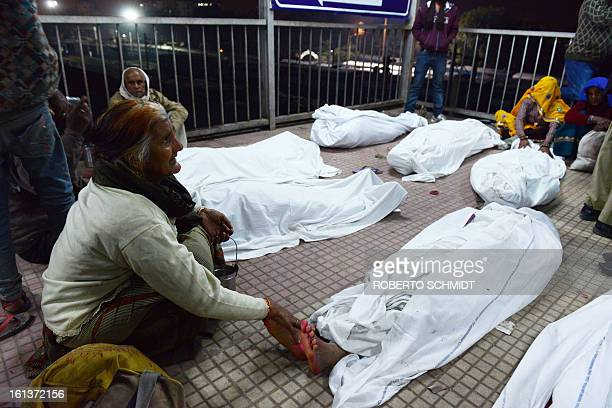 A woman caresses the foot of her dead relative that was killed during a stampede at the railway station in Allahabad on February 10 2013 At least 10...