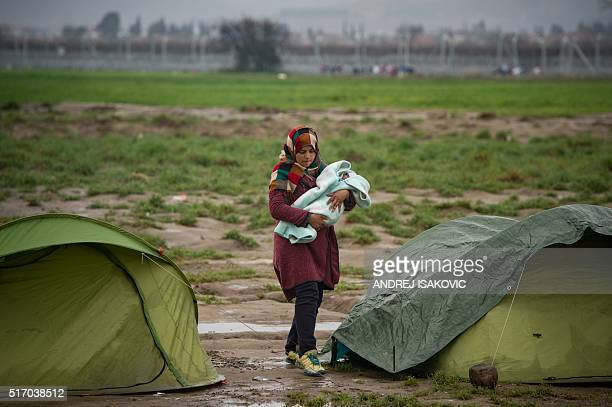 A woman caries a baby at a makeshift camp set by migrants and refugees at the GreekMacedonian border near the village of Idomeni on March 23 2016 /...