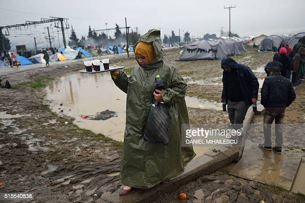 TOPSHOT A woman caries a tray of tea in a makeshift camp on March 14 2016 at the GreekMacedonian border near the Greek village of Idomeni where...