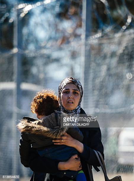 A woman caries her child as they walk along a razortopped fence to a registration camp after crossing the GreekMacedonian border near the town of...