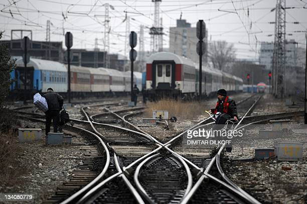 A woman caries her luggage across the tracks near the central railway station in Sofia on November 25 2011 Workers at Bulgaria's BDZ state railway...