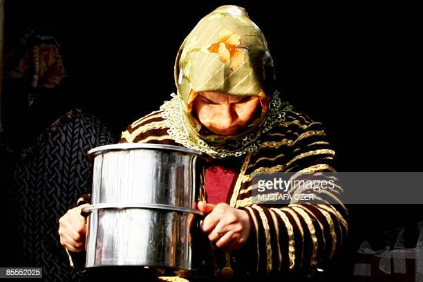 CHEVIRON A woman caries pots at the Eyup Sultan Municipality soup kitchen in where hundreds of poor people receive their food once a day in Istanbul...