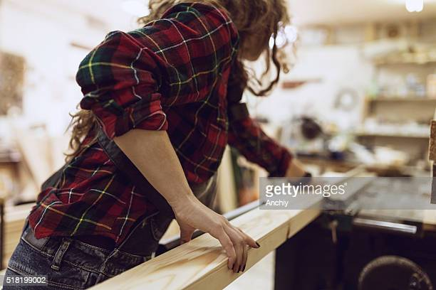 Woman Carpenter working on an electric buzz saw