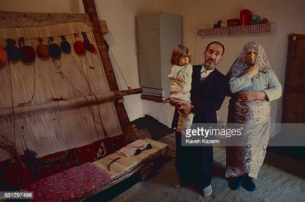 Woman carpet weaver stands with her husband who is holding their daughter in front of a carpet in process of being weaved in on 5th January, 1999 in...