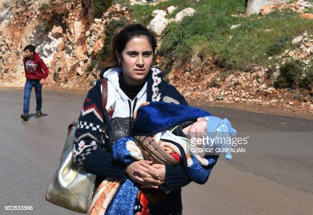 A woman carries a baby as civilians fleeing the city of Afrin in northern Syria walk at the mountainous road of alAhlam while heading towards the...