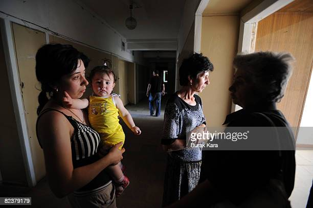 A woman carries a baby as Georgian refugees many of them from the breakaway province of South Ossetia walk up the steps of their refugee shelter...