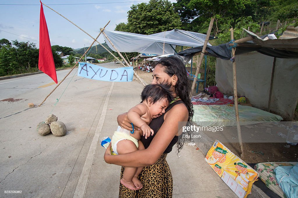 A woman carries a baby next to the highway after an earthquake struck Ecuador on April 21, 2016 in Pedernales, Ecuador. Some neighbours wait next to the highway to ask people for food. At least 400 people were killed after a 7.8-magnitude quake and the government's food supply is not reaching everyone.