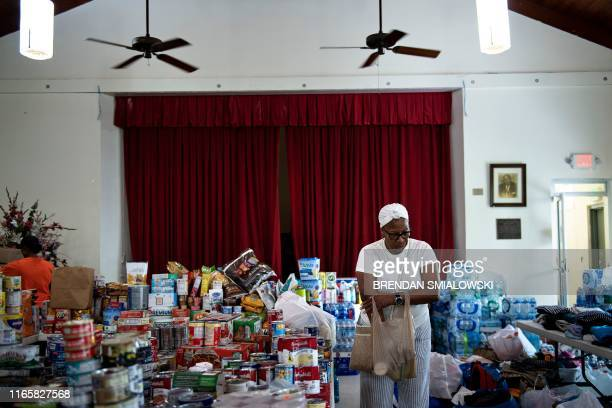 A woman carries a bag of canned goods as donations for Hurricane Dorian relief are received at Christ Episcopal Church on September 3 in Miami...