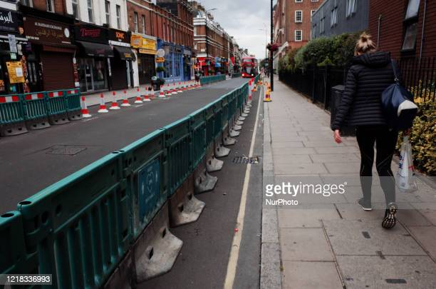 Woman carries a bag of food shopping beside barriers expanding the pavement to allow for easier social distancing on Praed Street near Paddington...