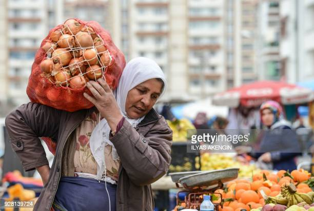 A woman carries a bag of onions as she works in a open bazaar in Diyarbakir on March 6 2018 / AFP PHOTO / ILYAS AKENGIN