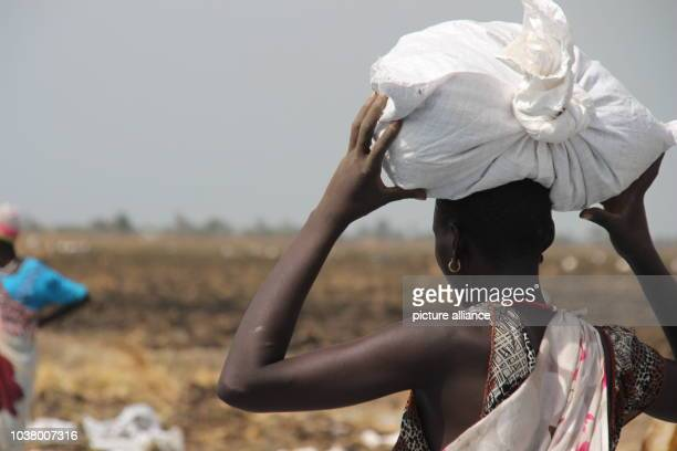 A woman carries a bag of relief supplies on her head in Ganyliel South Sudan 24 March 2017 It is located in the South Sudanese state of Unity the...