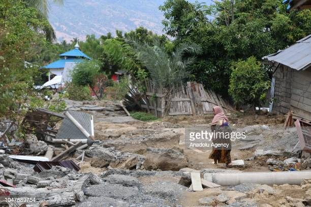Woman carries a bag on debris of buildings after an earthquake measuring 7.7 SR and the tsunami wave, in south of Palu, Sigi, Central Sulawesi,...